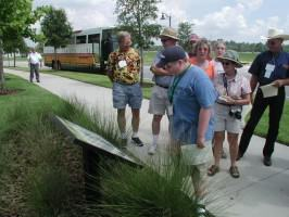 A tour group stops to read an educational sign about conservation practices implemented in the Town of Harmony, Florida. Photo by Mark Hostetler.