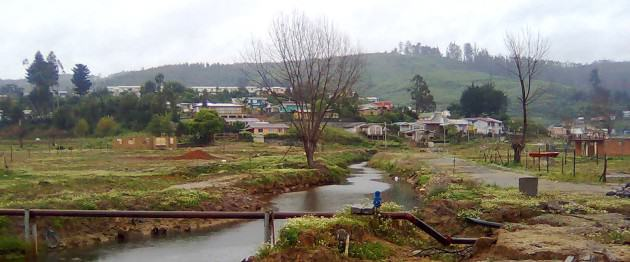 Figure 4. Effects of the tsunami in the urban space of Dichato. The image shows the remaining infrastructure (concrete bathrooms) after the tsunami and the hill at the back. Photo: Paula Villagra
