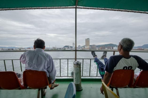 Two men leave the main city of Takamatsu, bound for Megijima on the last ferry. Photo: Patrick M. Lydon