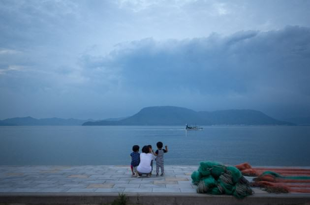 The only three children from the island wave to an incoming fishing boat. Photo: Patrick M. Lydon