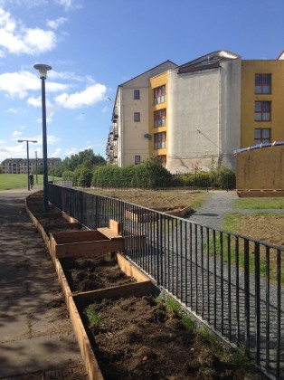 "In Clovenstone (Edinburgh), citizens supported by Wester Hailes Edible Estates have begun transforming a small triangle of sad looking grass into a community garden. They will retain the enclosing fence (which can make the area feel helpfully 'defensible') but they have also placed raised beds around the perimeter of the fence and have built a step ""so that no one hurts themselves climbing over the fence"". Photo: Janice Astbury"