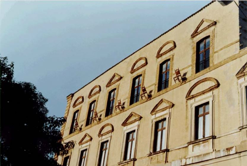 Five town hall chairs hung on the facade of the Palazzo Farnese (Ortona (Ps). Italy.1995. Photo (copyright): Emilio Fantin