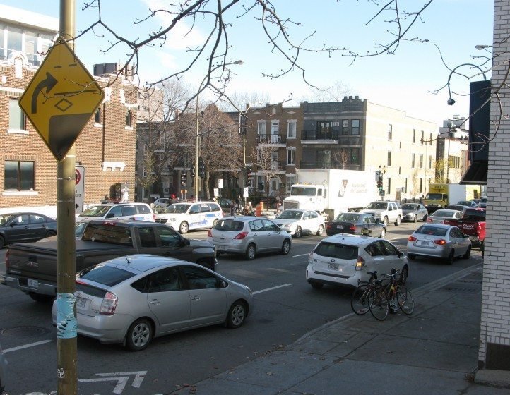 Intersection of two Montréal main streets where heavy vehicular traffic compromises walkability and livability, despite the many dwellings, shops and services lining both streets. Photo: Nik Luka