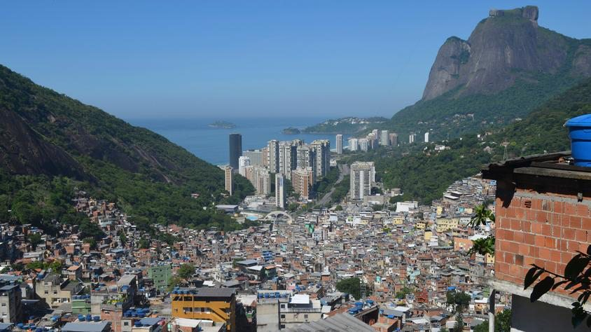 """Rocinha (""""little farm"""", due to its agricultural vocation until the mid 20th century), located in the rich southern zone of Rio de Janeiro, is considered one of the most populous favelas in Brazil. Most of its 70,000 inhabitants live in houses made from concrete and brick and have access to basic sanitation, plumbing, and electricity. The neighborhood has a vibrant local economy. Source: Alamy.com"""