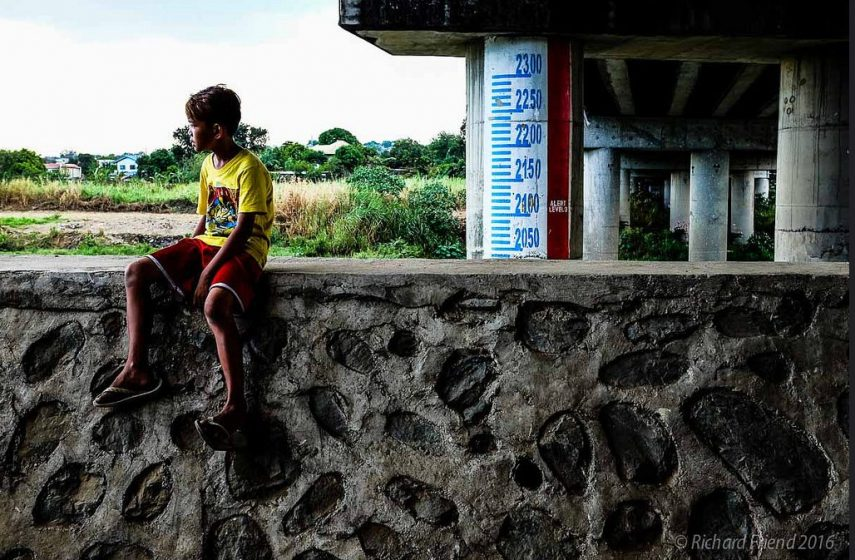 A young boy sits on top of a flood protection wall in Metro Manila. An informal community is settled under this bridge in a part of the river that is especially vulnerable to floods. Flood markers have been put in place to provide additional warning to the community - so that they can move to higher ground in case of an emergency. But the core of the problem is of lack of access to viable housing, employment and services that drives people to live in such vulnerable locations. Photo: © Richard Friend