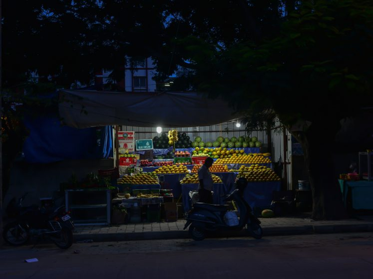 A lone fruit vendor waits for the last customers of the day, located strategically under a tree. Photo credit: Suri Venkatachalam