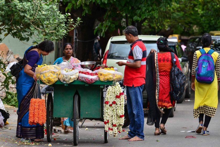 Customers conduct a close inspection of flower garlands under a neighbourhood tree. Photo credit: Suri Venkatachalam