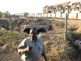 Housing built just beyond the NNP fence; Southern Bypass to be built along the dirt strip that still separates them. In the foreground is Michael Wanjau, then-Senior Warden for NNP. Photo: Glen Hyman
